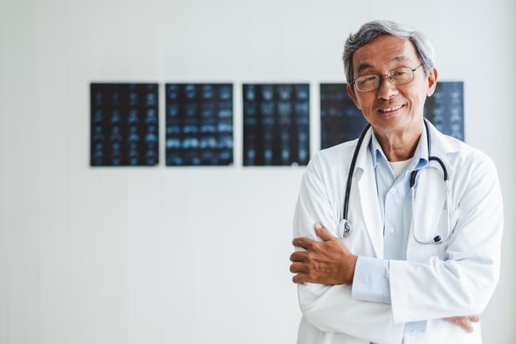 Asian doctor standing in front of xrays