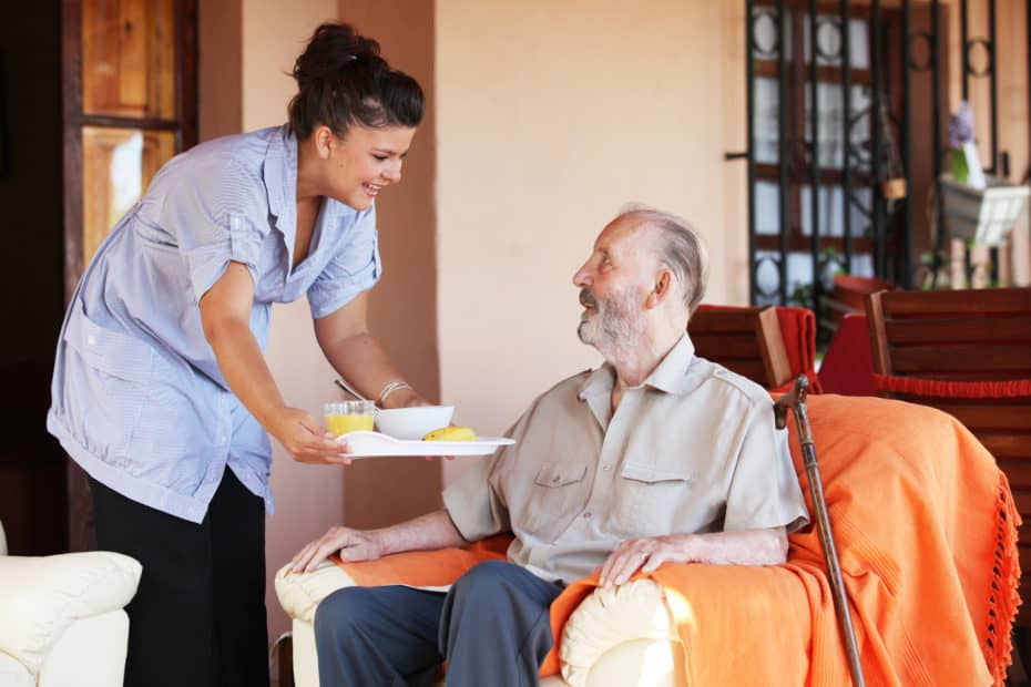 elderly senior being brought meal by a nurse