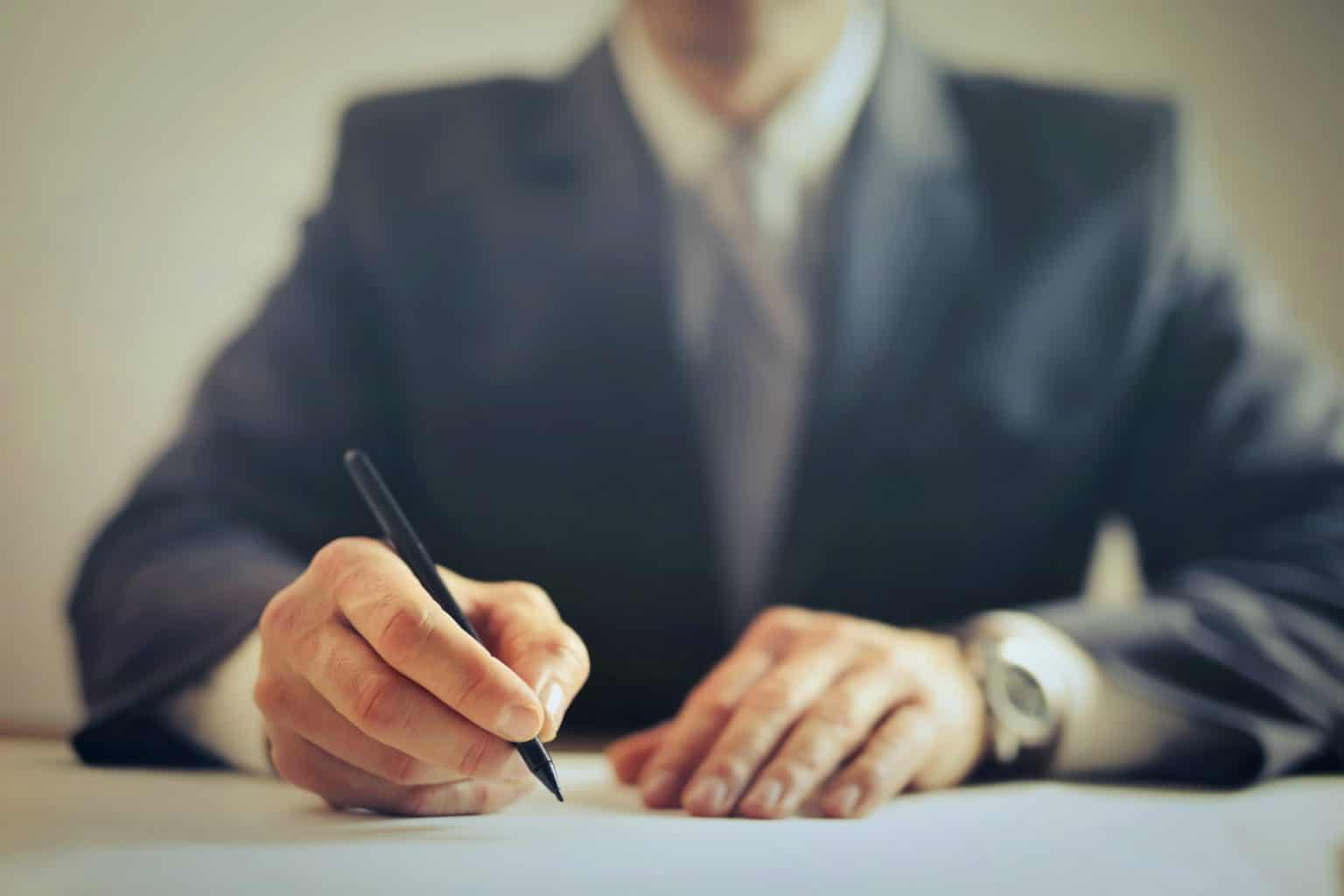man writing in suit