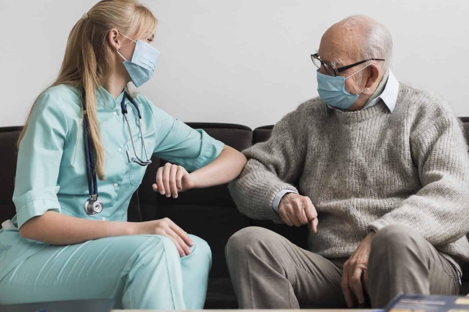female-nurse-elbow-touching-old-man-during-pandemic