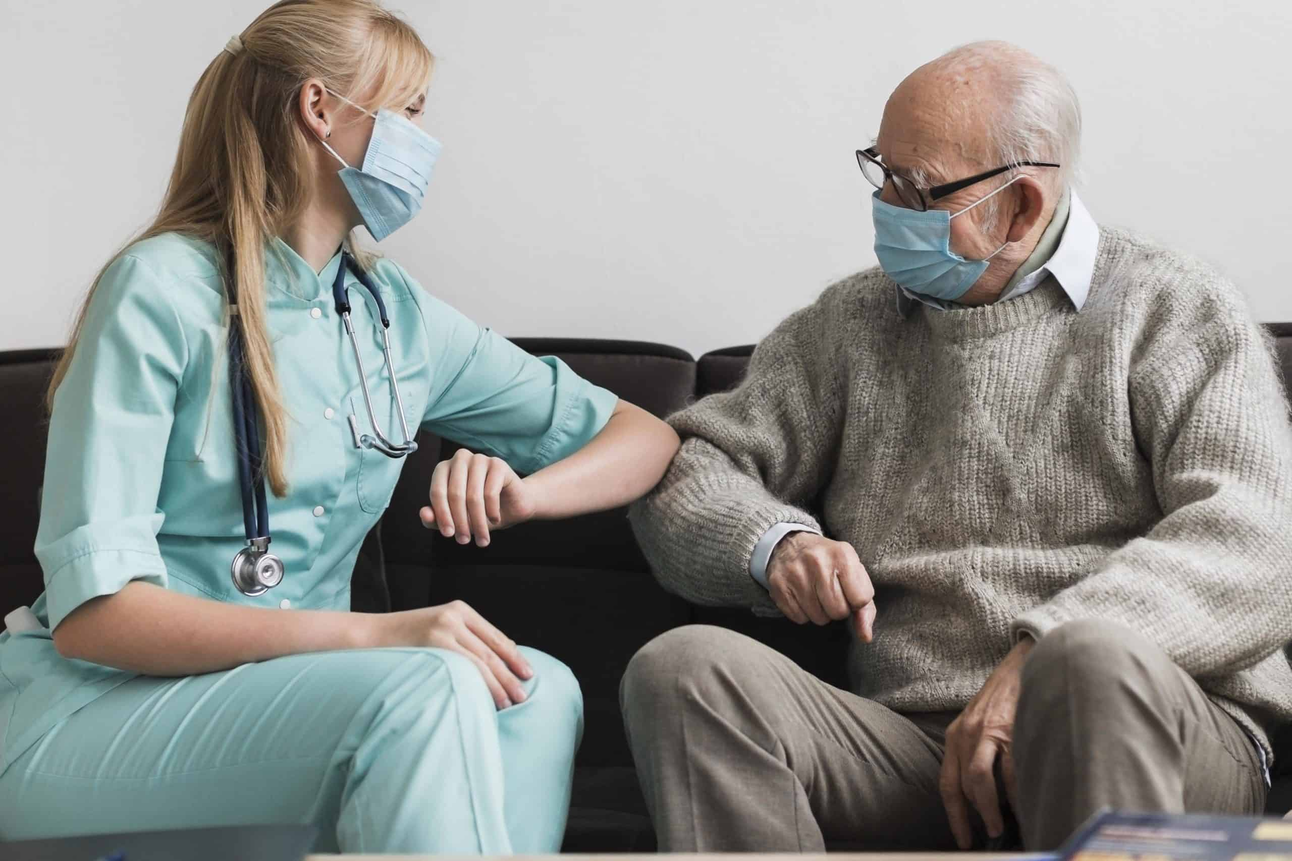 photograph of a nurse and an older man touching elbows