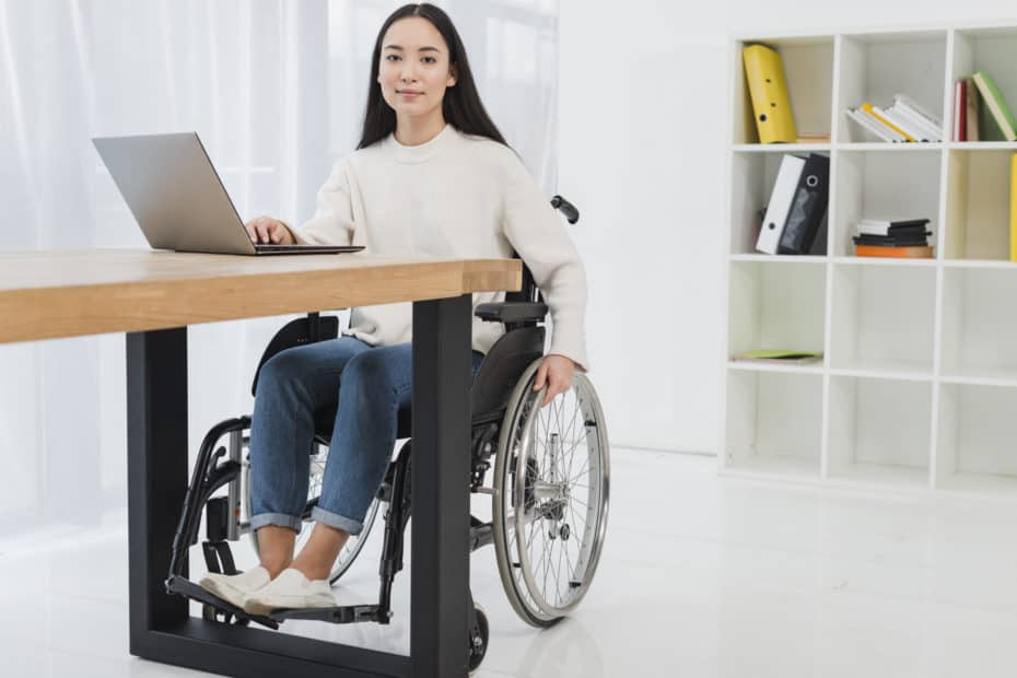 asian woman in a wheel chair sitting at a desk working on a laptop