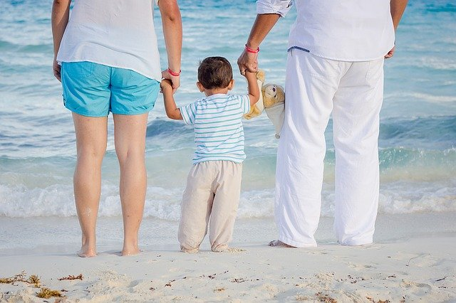 child on the beach holding his parents hands