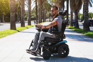 man in a motorized wheelchair moving down a sidewalk